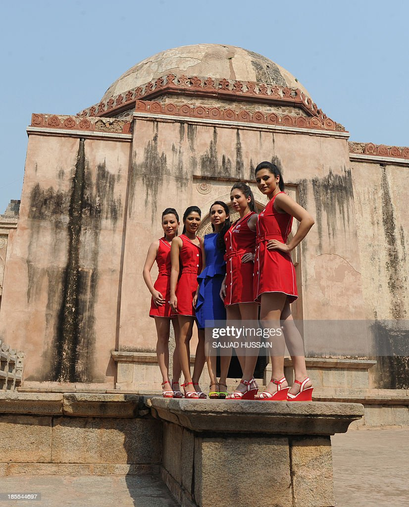 Indian designer Mendira Wirk (C) poses with models sporting Formula One paddock outfits during a promotional event at Hauz Khas village in New Delhi on October 22, 2013. The 2013 Formula One Grand Prix takes place in Greater Noida on the outskirts of New Delhi on October 27. AFP PHOTO/SAJJAD HUSSAIN