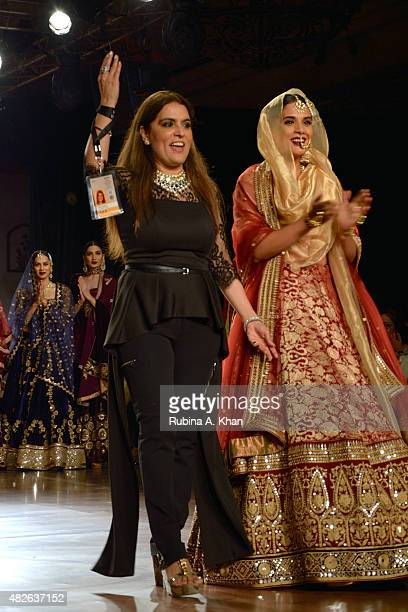 Indian designer Reynu Taandon waves next to Richa Chaddha on day four of the Fashion Design Council of India's Amazon India Couture Week 2015 on...