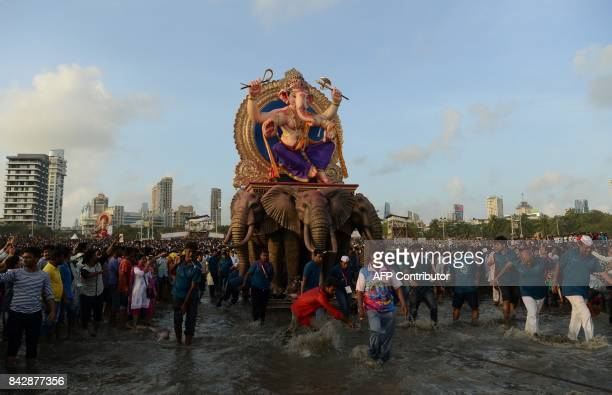 Indian devotees carry a statue of elephantheaded Hindu god Lord Ganesha for immersion in the Arabian sea in Mumbai on September 5 2017 During the...