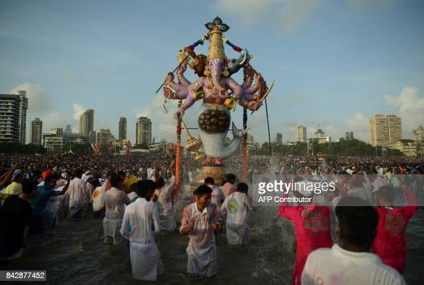 TOPSHOT Indian devotees carry a statue of elephantheaded Hindu god Lord Ganesha for immersion in the Arabian sea in Mumbai on September 5 2017 During...