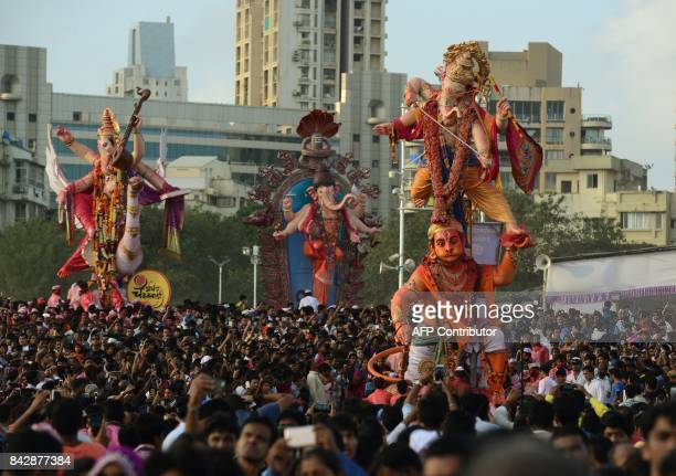 Indian devotees carry statues of elephantheaded Hindu god Lord Ganesha for immersion in the Arabian sea in Mumbai on September 5 2017 During the...