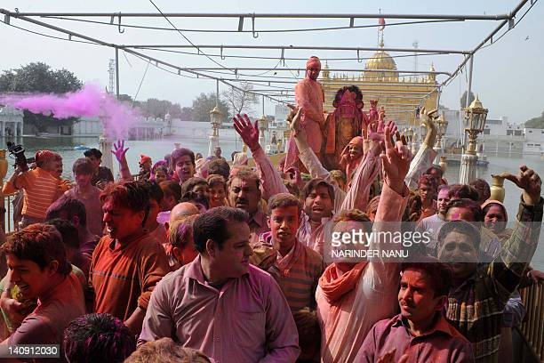 Indian devotees carrying an idol of Lord Krishna as they daub each other with coloured powder during Holi celebrations at the historical Durgiana...