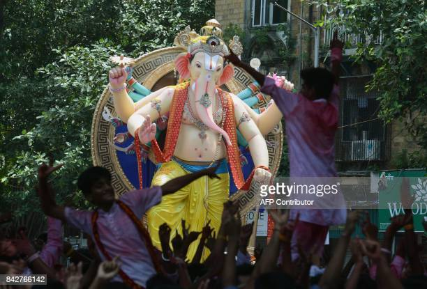 TOPSHOT Indian devotees dance around a huge idol of elephantheaded Hindu deity Ganesha during its procession for an immersion in Mumbai on September...
