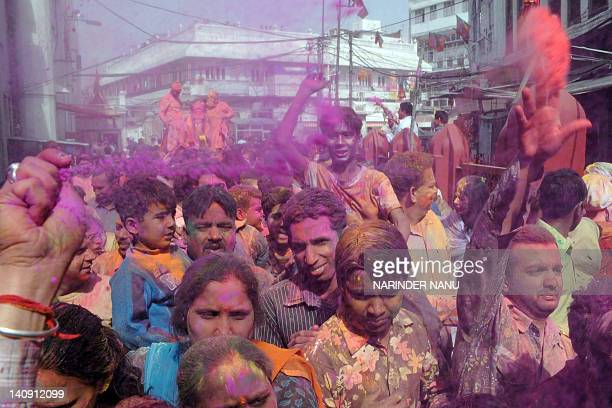 Indian devotees dance to drum beats as they daub each other with coloured powder at a procession with an idol of Lord Krishna during Holi...