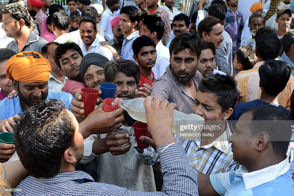 Indian devotees distribute liquor after giving offerings at the 'Samadh' or 'Mazar' (tomb) of Baba Rode Shah in the village of Bhoma Wadala, some 30 kms from Amritsar on March 24, 2013. Thousands of devotees from across the country offer alcohol at the tomb during the two day Babe Rode Shah Mela (Fair) in the northern Indian state of Punjab in the belief their lives will be enhanced in a variety of ways. AFP PHOTO/NARINDER NANU