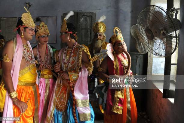 Indian devotees dressed as the Hindu gods Lord Krishna and Ganesh wait to take part in a procession on the eve of 'Janmashtami' marking the birth of...