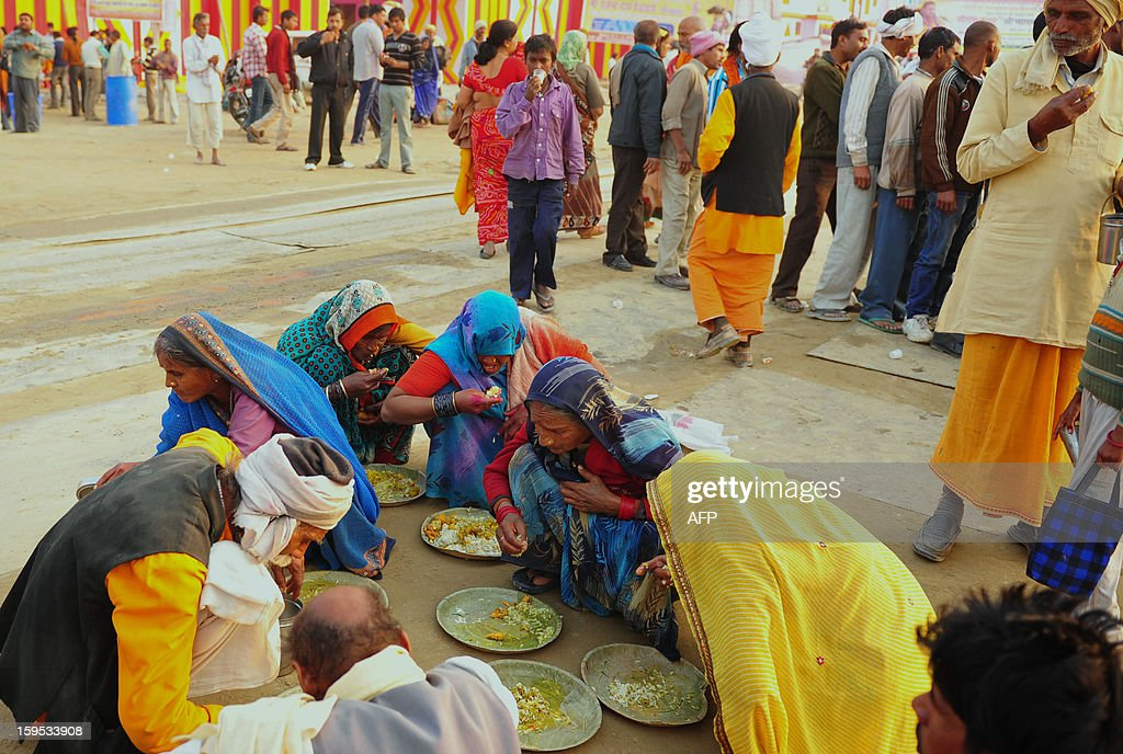 Indian devotees eat 'bhandra' outside a religious camp during the Kumbh Mela Festival alongside the Sangam in Allahabad on January 15, 2013. The Kumbh Mela in the Indian town of Allahabad will see up to 100 million worshippers gather over the next 55 days to take a ritual bath in the holy waters, believed to cleanse sins and bestow blessings. AFP PHOTO/ Sanjay KANOJIA