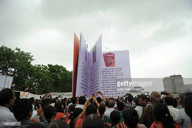 Indian devotees from the Jain community look at a huge replica of the 'Kadve Pravachan' religious book during its launch in Ahmedabad on July 28 2012...