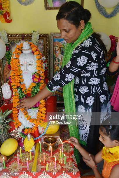 Indian devotees garland an idol of Bhagwan Valmiki at a temple in Amritsar on October 5 2017 Devotees celebrate on the occasion of the birth...