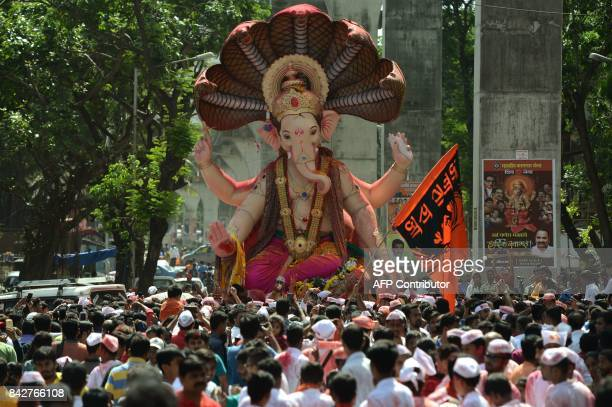 Indian devotees gather around a huge idol of elephantheaded Hindu deity Ganesha during its procession for an immersion in Mumbai on September 5 2017...
