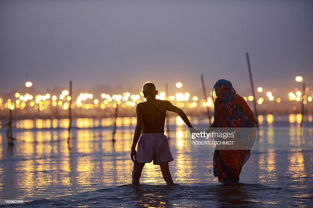 Indian devotees hold hands as they walk in the waters of Sangam or confluence of the Yamuna, Ganges and mythical Sarawati rivers at sunset during the Maha Kumbh festival in Allahabad on February 8, 2013. The Kumbh Mela in the town of Allahabad will see up to 100 million worshippers gather over 55 days to take a ritual bath in the holy waters, believed to cleanse sins and bestow blessings.