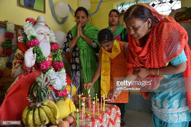 Indian devotees light candles as they pay respect to a idol of Bhagwan Valmiki at a temple in Amritsar on October 5 2017 Devotees celebrate on the...