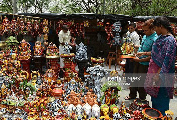 Indian devotees look at a statue of Hindu God Lord Krishna at a roadside stall in Hyderabad on August 16 ahead of The Janmashtami Festival which...