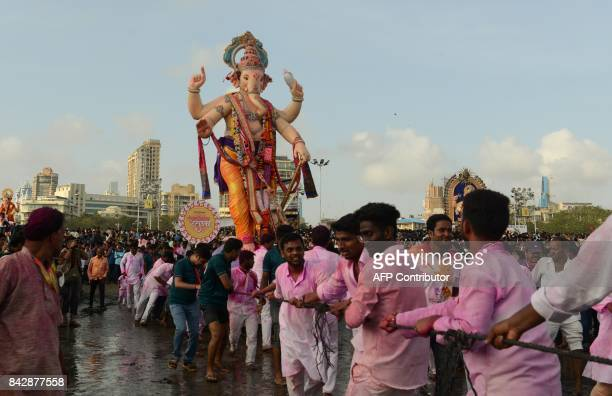Indian devotees move a statue of elephantheaded Hindu god Lord Ganesha to be immersed in the Arabian sea in Mumbai on September 5 2017 During the...