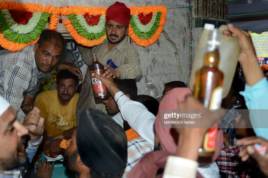 Indian devotees offer liquor at the 'Samadh' or 'Mazar' (tomb) of Baba Rode Shah in the village of Bhoma Wadala, some 30 kms from Amritsar on March 24, 2013. Thousands of devotees from across the country offer alcohol at the tomb during the two day Babe Rode Shah Mela (Fair) in the northern Indian state of Punjab in the belief their lives will be enhanced in a variety of ways.
