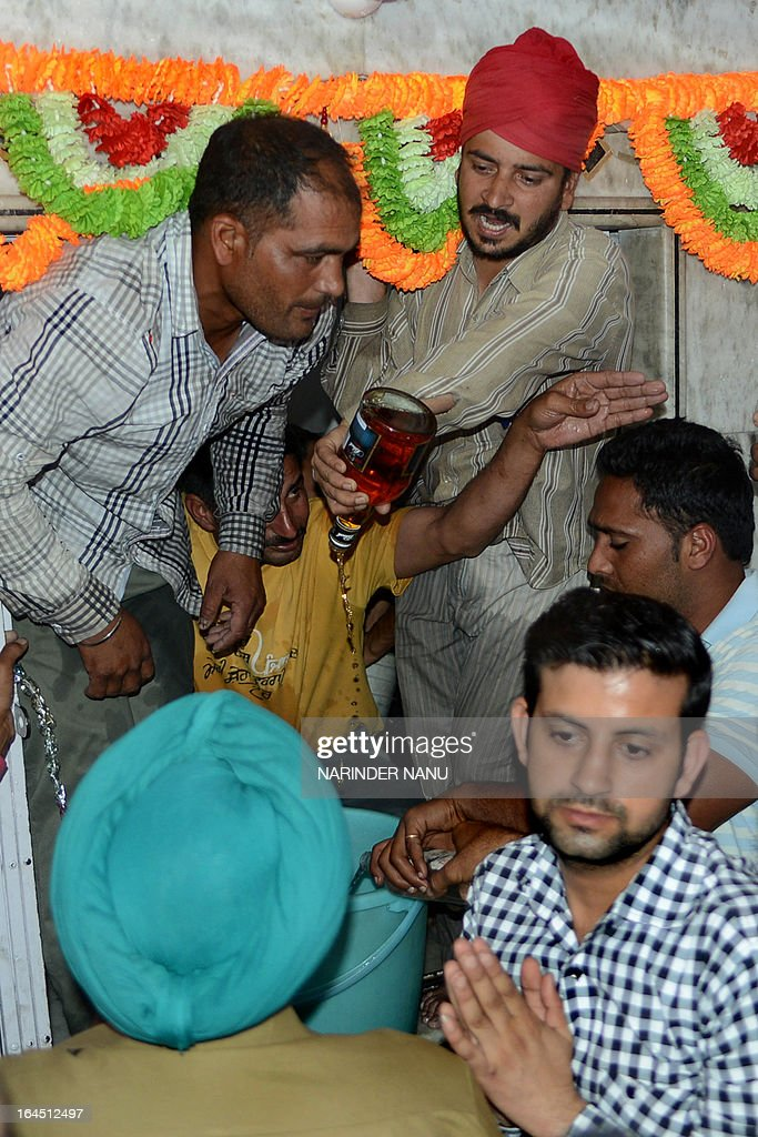 Indian devotees offer liquor at the 'Samadh' or 'Mazar' (tomb) of Baba Rode Shah in the village of Bhoma Wadala, some 30 kms from Amritsar on March 24, 2013. Thousands of devotees from across the country offer alcohol at the tomb during the two day Babe Rode Shah Mela (Fair) in the northern Indian state of Punjab in the belief their lives will be enhanced in a variety of ways. AFP PHOTO/NARINDER NANU