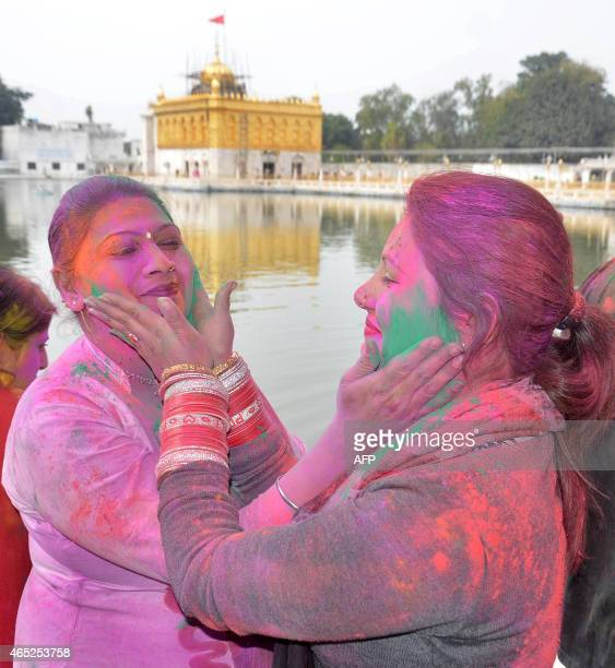 Indian devotees play with color during celebrations of 'Holi' at the Durgiayana Temple in Amritsar on March 5 2015 'Holi' the festival of colours is...