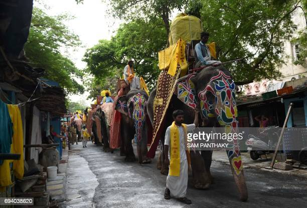 TOPSHOT Indian devotees ride decorated elephants as they take part in the Lord Jagannath Jal Yatra in Ahmedabad on June 9 2017 / AFP PHOTO / SAM...