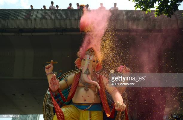 Indian devotees shower rose petals and coloured powder on a huge idol of elephantheaded Hindu deity Ganesha during its procession for an immersion in...