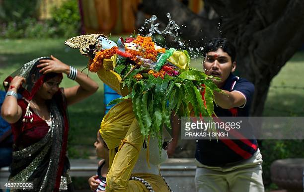 Indian devotees sprinkles water onto a tableau of the Hindu god Lord Krishna at a temple on the ocassion of 'Janmashtami' in New Delhi on August 18...
