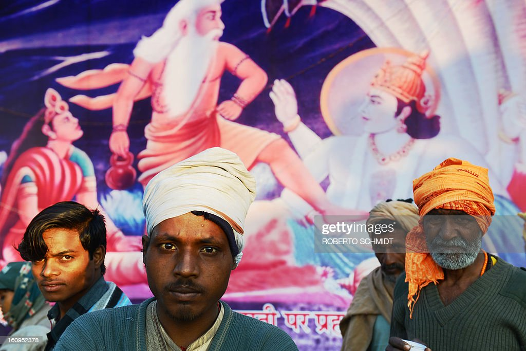 Indian devotees stand next to a painting depicting Hindu gods in confrontation at the entrance of one of hundreds of camps set up by different Hindu religious factions during the Maha Kumbh Mela festival in Allahabad on February 8, 2013. The Kumbh Mela in the town of Allahabad will see up to 100 million worshippers gather over 55 days to take a ritual bath in the holy waters, believed to cleanse sins and bestow blessings.