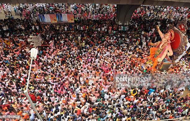 Indian devotees throng the streets as a huge idol of elephantheaded Hindu god Lord Ganesha is brought on procession for an immersion in Mumbai on...