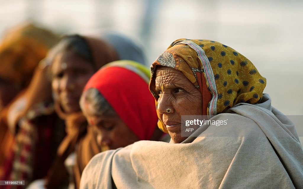 Indian devotees wait for free food near Sangam or confluence of the Yamuna, Ganges and mythical Saraswati rivers during the Kumbh Mela festival in Allahabad on February 18, 2013. The Kumbh Mela in the town of Allahabad will see up to 100 million worshippers gather over 55 days to take a ritual bath in the holy waters, believed to cleanse sins and bestow blessings.