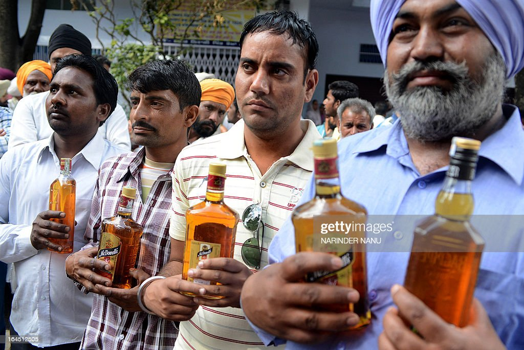 Indian devotees waits to offer liquor at the 'Samadh' or 'Mazar' (tomb) of Baba Rode Shah in the village of Bhoma Wadala, some 30 kms from Amritsar on March 24, 2013. Thousands of devotees from across the country offer alcohol at the tomb during the two day Babe Rode Shah Mela (Fair) in the northern Indian state of Punjab in the belief their lives will be enhanced in a variety of ways.