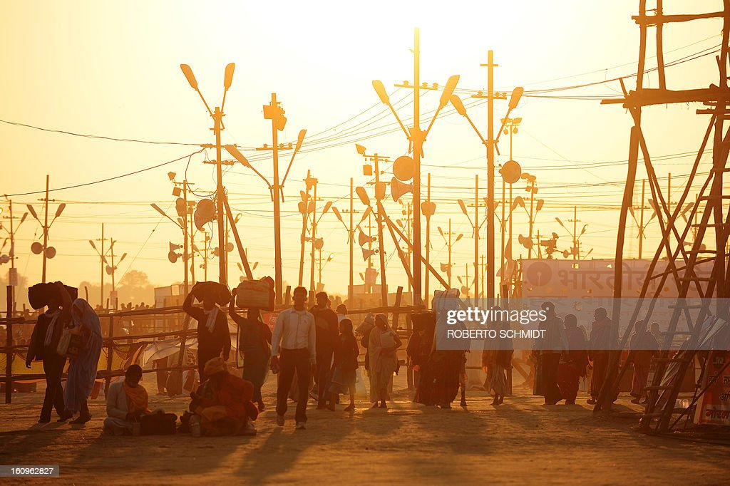 Indian devotees walk at sunset during the Maha Kumbh festival in Allahabad on February 8, 2013. The Kumbh Mela in the town of Allahabad will see up to 100 million worshippers gather over 55 days to take a ritual bath in the holy waters, believed to cleanse sins and bestow blessings.