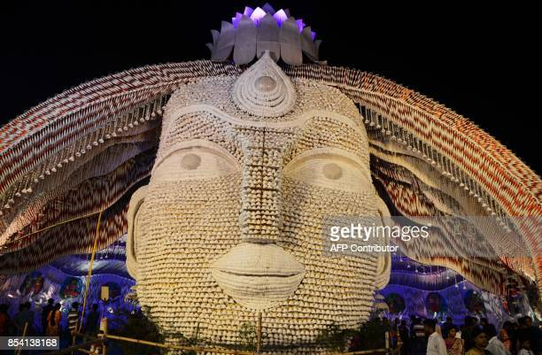 Indian devotees walk inside a temporary structure called 'pandal' to worship Goddess Durga during 'Durga Puja' festival celebrations in Siliguri on...