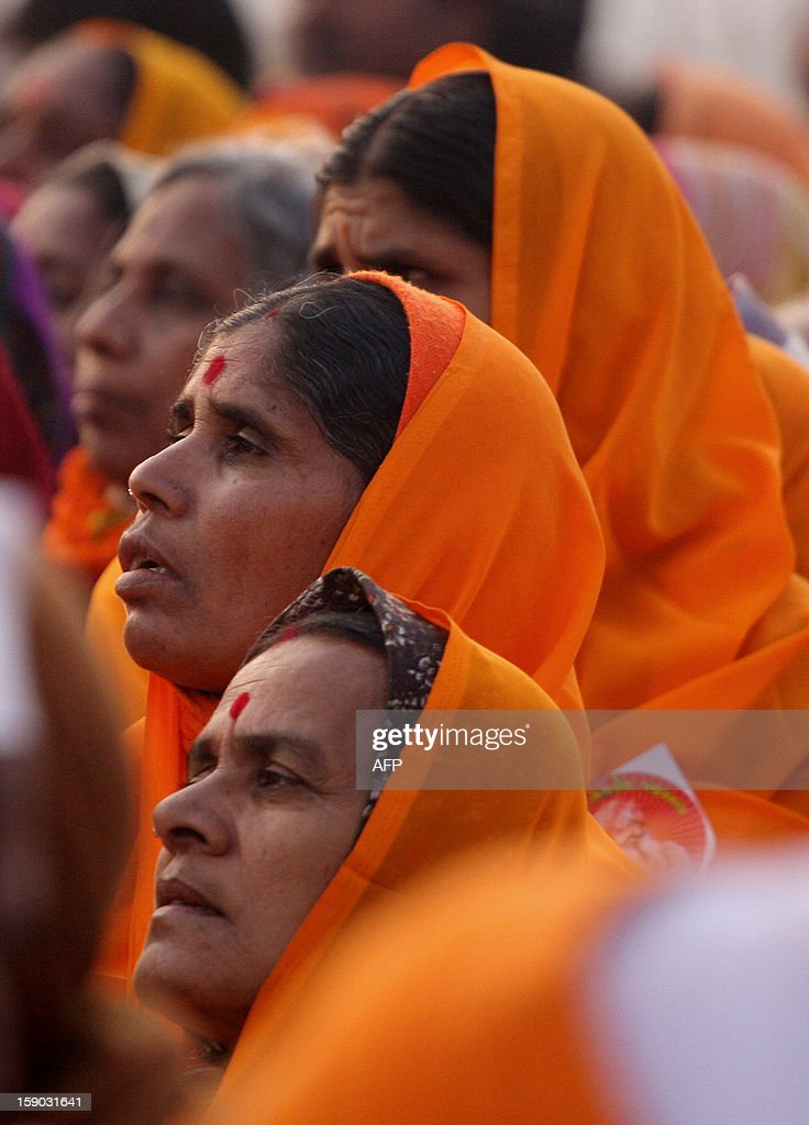 Indian devotees watch as Naga Sadhus - holy men - of Shri Panchayati Anand Akhara participate in a religious procession as the first 'royal entry' for the Kumbh Mela at Sangam in Allahabad on January 6, 2013. The Kumbh Mela, which is scheduled to take place in the northern Indian city in January and February 2013, is the world's largest gathering of people for a religious purpose and millions of people gather for this auspicious occasion. AFP PHOTO/Sanjay KANOJIA