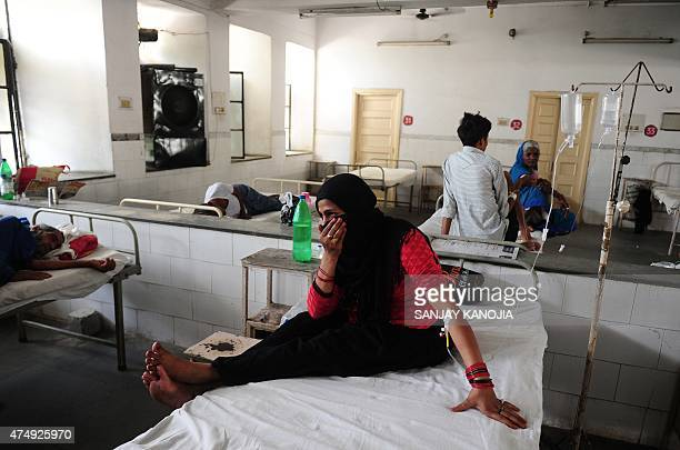 Indian diarrhoea patient Nansi Bano gestures as she sit on a bed in a government hospital in Allahabad on May 28 as scorching weather conditions...