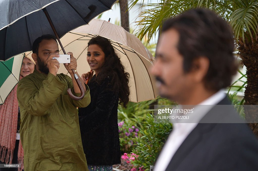 Indian director Amit Kumar (L) takes pictures of Indian actor Nawazuddin Siddiqui with his mobile phone during the photocall of the movie 'Monsoon Shootout' presented out of competition as part of the 66th Cannes film festival on May 18, 2013 in Cannes. AFP PHOTO / ALBERTO PIZZOLI