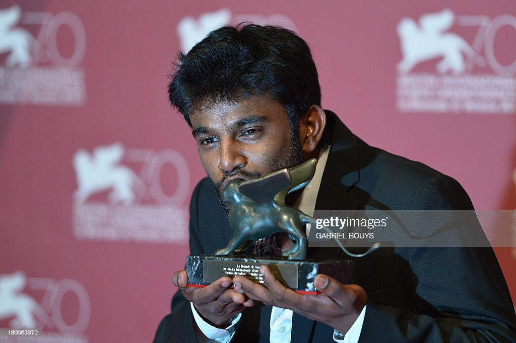 Indian director Shubhashish Bhutiani receives the Orizzonti award for best short from Belgian director Frederic Fonteyne for his movie 'Kush' during the award ceremony of the 70th Venice Film Festival on September 7, 2013 at Venice Lido.