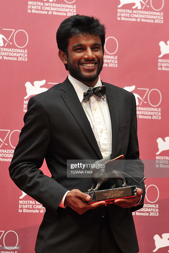 Indian director Shubhashish Bhutiani receives the Orizzonti award for best short from Belgian director Frederic Fonteyne for his movie 'Kush' during a photocall at the award ceremony of the 70th Venice Film Festival on September 7, 2013 at Venice Lido.