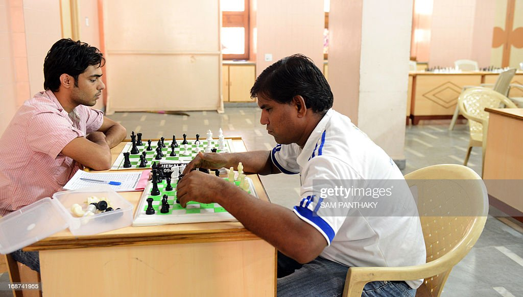 Indian disabled chess player, Ibrahim Ingar (R), plays a match against Anshul Uppal on the first day of Brain Power U-2000 International Rating Tournament, at the SGVP International School on the outskirts of Ahmedabad on May 14, 2013. Some 340 players from across India are participating in this tournament. AFP PHOTO/ Sam PANTHAKY