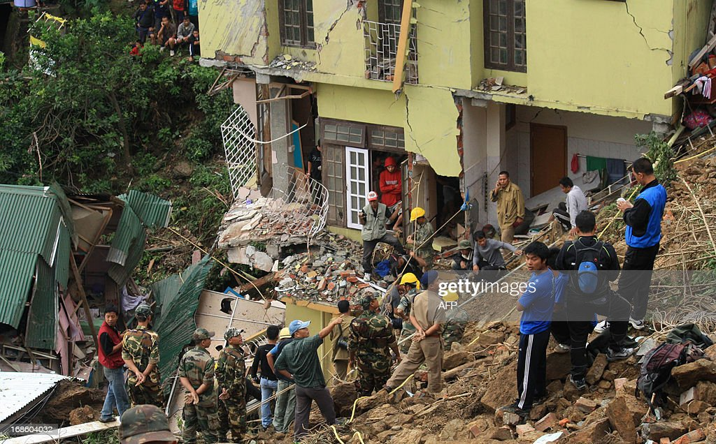 Indian Disaster Response Force and security personnel carry out rescue operations at the site of a landslide in Aizawl, in the eastern state of Mizoram on May 12, 2013. A landslide which was triggered by a cyclonic storm and heavy pre-monsoon rain in the Indian eastern city of Aizawl destroy more than 10 residential building and killed 10 persons and seven missing, according to news report. AFP PHOTO/ Caisii Mao