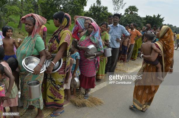 Indian dispersed villagers queue to collect food aid after their homes were flooded in Malda in the West Bengal state of West Bengal on August 24...