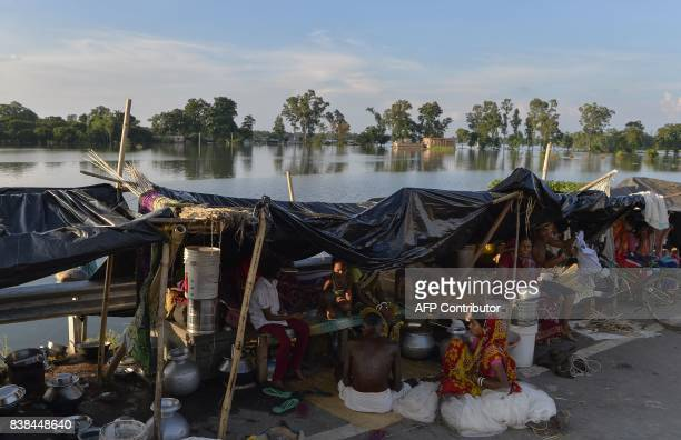 Indian dispersed villagers rest in temporary tents on the roadside in Malda in the Indian state of West Bengal on August 24 2017 The death toll from...
