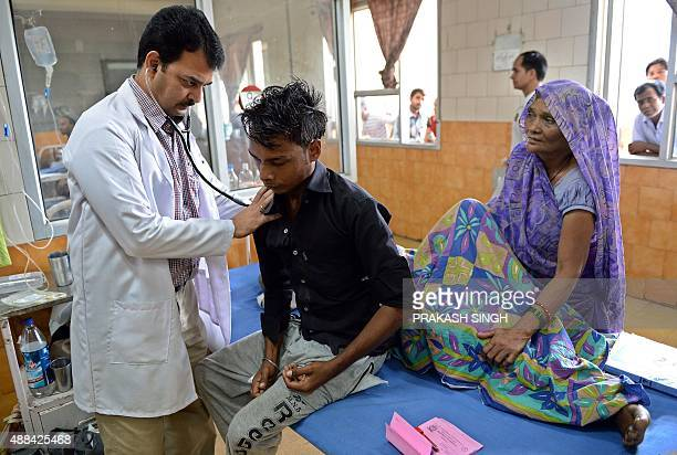 Indian doctor Hemant Sharma checks a dengue patient in The Hindu Rao hospital in New Delhi on September 16 2015 The Indian capital is reeling from...