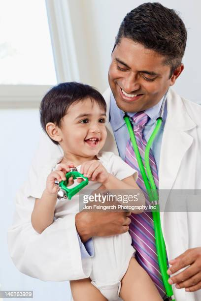 Indian doctor holding baby in doctor's office