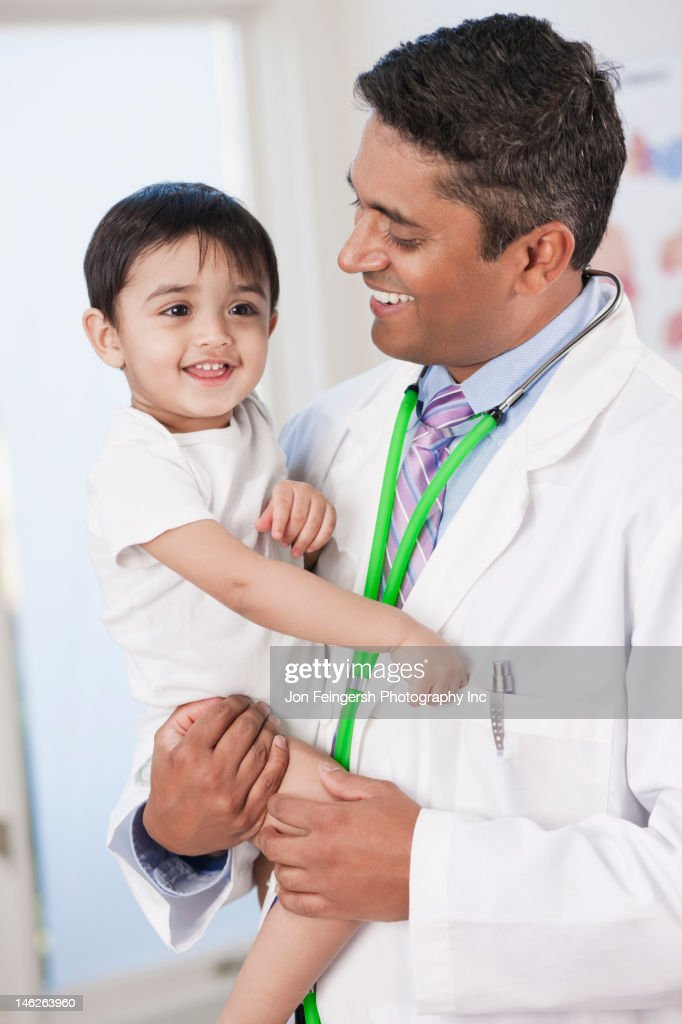 Indian doctor holding baby in doctor's office : Stock Photo