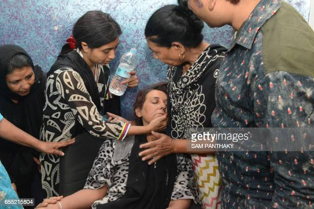 Indian domestic worker Hafijabanu Rajabhusen is given water after collapsing at a press conference following her return from Saudi Arabia in...