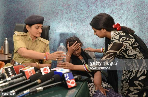 Indian domestic worker Hafijabanu Rajabhusen is offered water at a press conference following her return from Saudi Arabia in Ahmedabad on March 19...