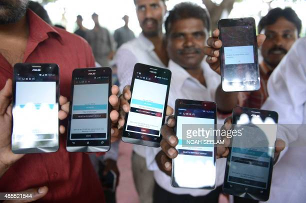 Indian drivers for Uber show mobiles phones given to them by the company during a oneday hunger strike against the USheadquartered transportation...
