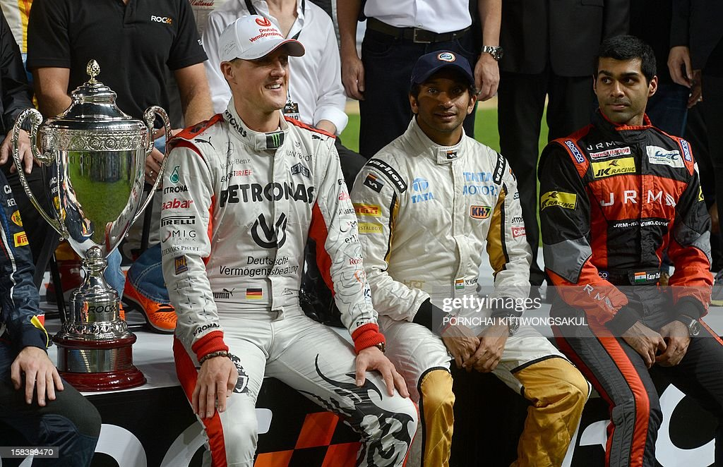 Indian drivers Karun Chandhok (L) and Narain Karthikeyan (C) sit next to German F1 driver and seven times World champion Michael Schumacher (R) during the Race of Champions (ROC) Nations Cup Drivers 's Presentation at Rajamangala Stadium in Bangkok on December 15, 2012. The Race of Champions (ROC) will take place in Thailand between December 14 and 16 and brings together heavyweights from all motor racing disciplines in the same type of car.