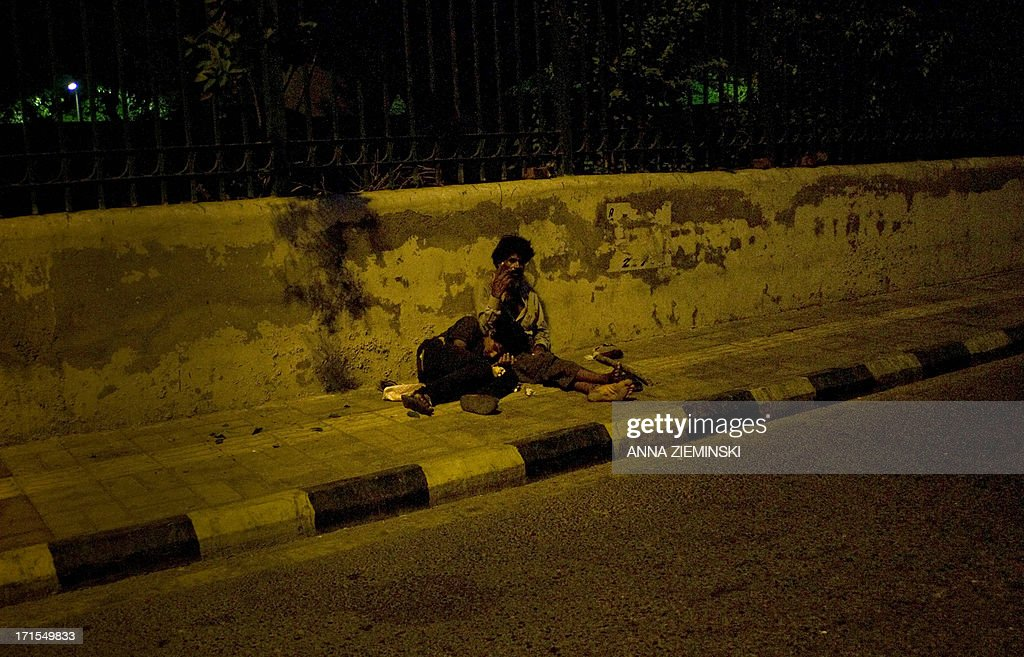 Indian drug addicts rest at the roadside in New Delhi on June 26, 2013, on the International Day Against Drug Abuse and Illicit Trafficking. Activists in the city launched the 'Support Don't Punish' campaign calling for the removal of legal sanctions on low-level drug offenses and encouraging 'harm reduction' services such as needle exchange and opoid substitution therapy. AFP PHOTO/ Anna ZIEMINSKI