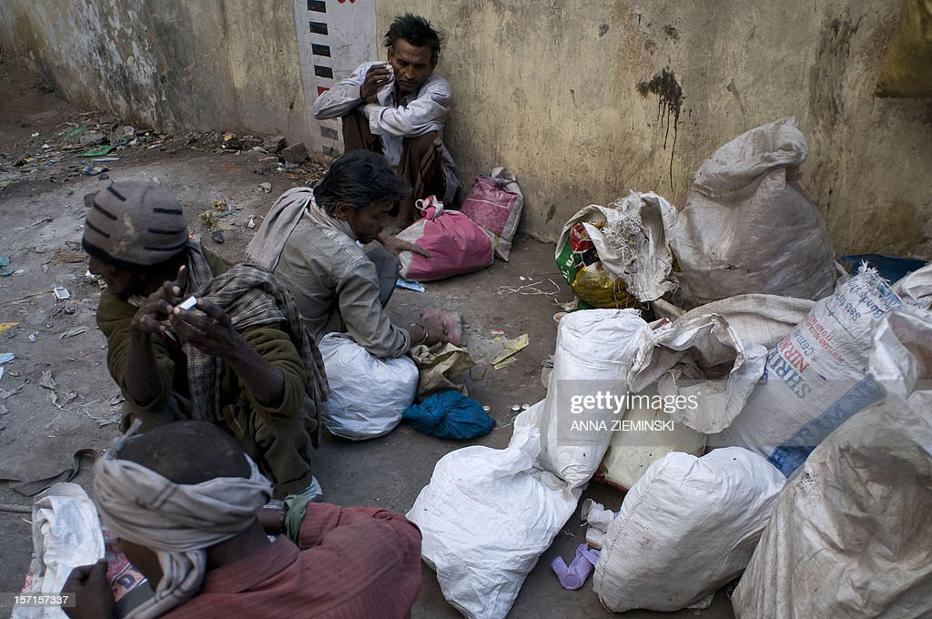 Indian drug users sort out recycling which pays for their habit in the old sector of New Delhi on November 29, 2012. Injecting drug users (IDU'Ss) are at high risk of contracting HIV/AIDS as blood transfer through the sharing of infected needles is an extremely effective way of transmitting HIV. AFP PHOTO/ Anna ZIEMINSKI