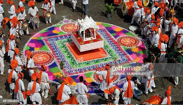 Indian drummers in traditional attire play on around a rangoli design during a procession celebrating 'Gudi Padwa' or the Maharashtrian new year in...