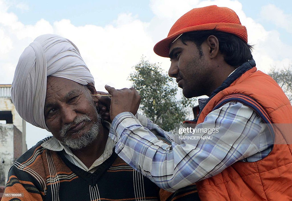 Indian ear-cleaner Sunil Kumar (R) tends to a customer on the road in Amritsar on February 27, 2013. Ear-cleaners, or Kaan Saaf Wallahs as they are locally known, are a common sight in Indian cities where customers pay to have wax and dirt scraped from inside their ears.